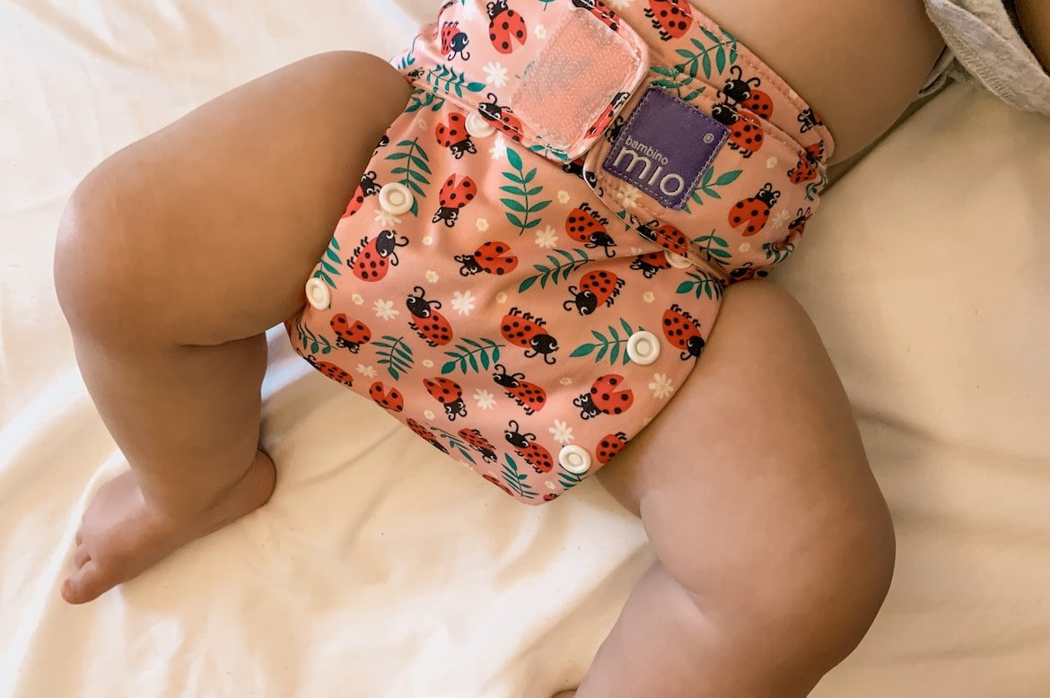 baby wearing an all-in-one cloth diaper