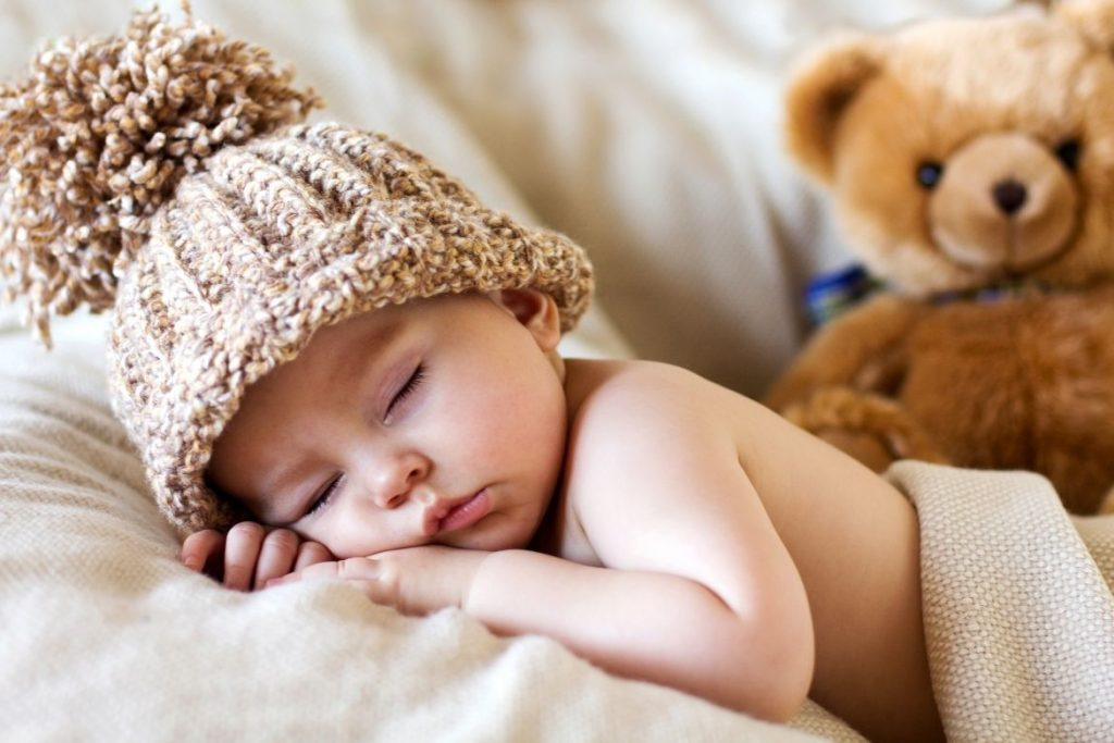 Sleeping baby wearing a warm hat